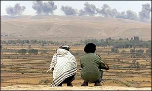 Northern Alliance fighters watch the explosions
