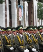 Turkmen soldiers wait beneath a poster of their president
