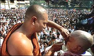 Buddhist monk shaves moustache of Ram Raj, right, chairman of All India Confederation of Schedule Castes and Tribes