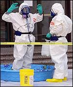Hazardous materials experts decontaminate each other after leaving the Hart Senate building, AFP