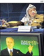 Palestinian leader Yasser Arafat listens to a speech by Israeli Foreign Minister Shimon Peres in Spain on Saturday