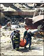Firefighters recover a body from the WTC rubble