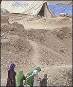Afghan refugees with a UNHCR tent in the background