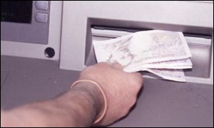 Customer getting cash from an ATM machine, BBC