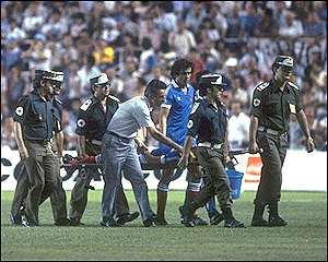 France's Michel Platini looks on as Patrick Battiston is stretchered off unconcious after a horrific clash