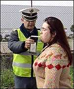 Policeman conducts breathalyser test