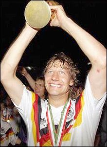Guido Buchwald holds the World Cup above his head as Germany celebtrate their third world title