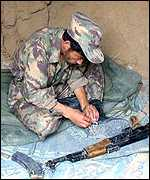 A Northern Alliance fighter checks his gun