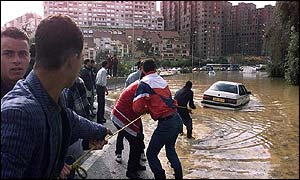 Residents try to tow a car off a flooded road in Dely Ibrahim, near Algiers,
