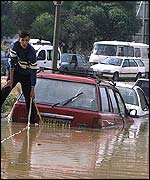 A resident tries to tow his car away from a flooded road in Dely Ibrahim