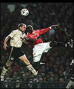[ image: Dwight Yorke challenges for a ball with Eddie Youds]