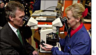 Tom Daschle looks at anthrax through a microscope