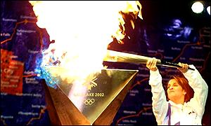 A torchbearer takes a light from the Olympic flame