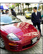 Passers-by look at an imported Japanese car in Shanghai