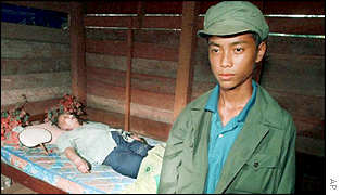 A Khmer Rouge soldier guards the body of Pol Pot , 16 April 1998