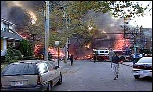 Flames and people on the street at the scene of the crash