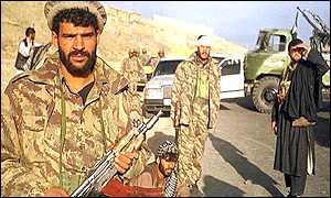 Uniformed fighters of Northern Alliance wait at the entrance of Afghanistan capital