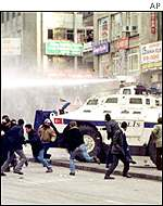 Police armoured vehicle uses water cannon to disperse rioters in support of the hunger strikers