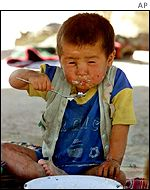 A Tajik child feeds itself