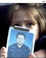 A Serbian girl holding a picture of her missing father