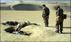 Northern Alliance fighters view Taleban corpses near Kunduz