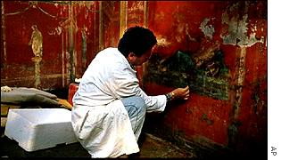 An archaeologist restores a fresco in an ancient Roman guest house in Pompeii