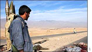 Northern Alliance fighter looks at the bodies of dead Taleban