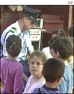 A policeman with Israeli children in a kindergarten near where a Palestinian shot dead an Israeli