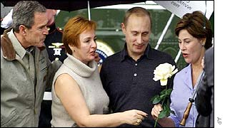 Lyudmila Putin presents a flower to Laura Bush as their husbands look on