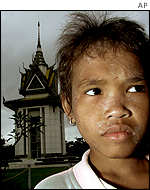 Unidentified young Cambodian girl stands in front of a Killing Fields memorial
