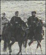 grainy image of men on horseback