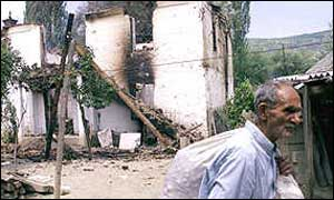 A returning Kosovo Albanian walking past a burnt out Serb house