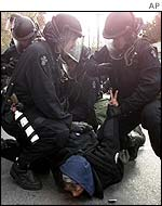 Riot police bring down a protester