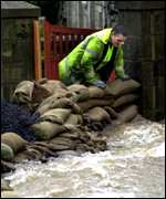 Man with sandbags in flood   PA