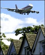 A passenger airliner passing over rooftops as it arrives at Heathrow Airport