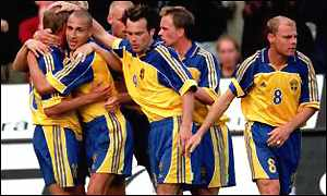 Swedish players surround Marcus Allback, after he scores during a qualifier