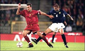 Marc Wilmots evades the challenge of Dominic Matteo in a Belgium v Scotland match