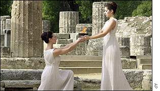 Greek actresses dressed as high priestesses hold the Olympic flame