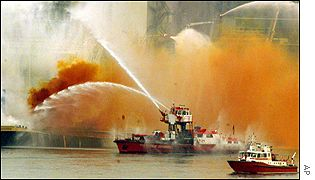 Orange smoke billows as fire boats try to extinguish the blaze