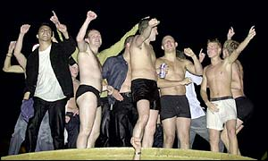 Football fans celebrate in a fountain