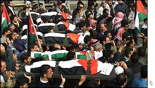 Mourners carry the schoolboys' coffins draped in the Palestinian flag