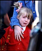 Distraught Allison Lea, aged five, being escorted to school