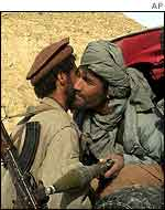 Northern Alliance fighter embraces an Afghan defector