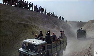 Northern Alliance soldiers watch a column of Taleban trucks