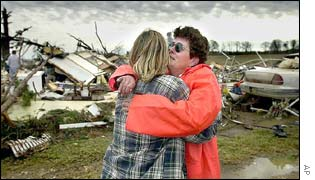 Two women hugging in front of destroyed house