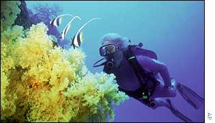Jean Michel Cousteau diving at coral reef near Fiji