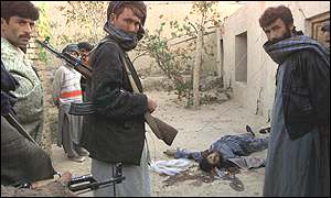 Northern Alliance fighters guard a non-Afghan Taleban man killed during the battle