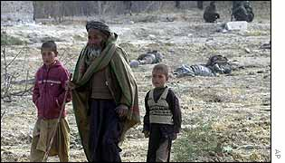 An Afghan man and two boys walk through the field covered with lifeless bodies of pro-Taliban forces in the fortress near Mazar-e-Sharif