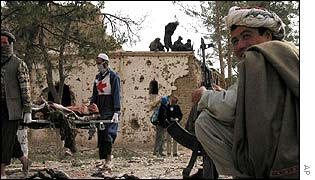 A Northern Alliance fighter looks on, as local Red Cross workers carry away bodies of pro-Taliban fighters