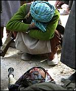 A Northern Alliance fighter cries over the body of a killed relative